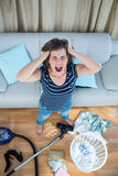 Ilsken kvinna i en kaotisk vardagsrum med dammsugare Royaltyfri Bild