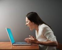 Ilsken kvinna med bärbara datorn arkivfoton