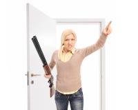 Ilsken kvinna med geväret som hotar någon Royaltyfri Foto