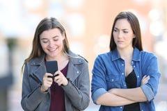 Ilsken kvinna med hennes vän som använder telefonen royaltyfri foto