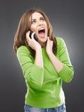 Ilsken kvinna med telefonen Royaltyfria Bilder