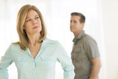 Ilsken kvinna som bort hemma ser med mannen i bakgrund arkivbild