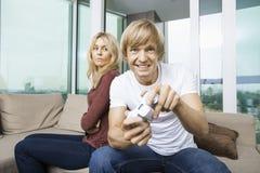 Ilsken kvinna som hemma ser manlekvideospelet i vardagsrum Royaltyfria Bilder