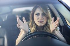 Ilsken kvinna som kör en bil arkivfoto