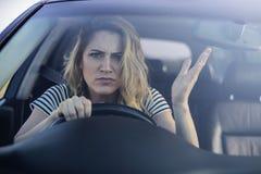 Ilsken kvinna som kör en bil royaltyfri foto