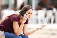 Ilsken kvinna som kallar på telefonen i gatan Royaltyfri Bild