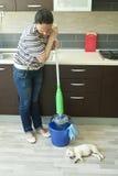 Ilsken kvinna som pressar golvmopp nära valp Royaltyfri Fotografi