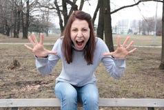 Ilsken kvinna som skriker med händer upp Arkivfoton