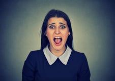 Ilsken kvinna som skriker på kameran fotografering för bildbyråer