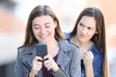 Ilsken kvinna som spionerar hennes vän som använder telefonen arkivfoto