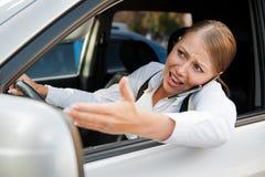 Ilsken kvinnlig som kör bilen Fotografering för Bildbyråer