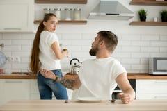 Ilsken make och chockad fru som argumenterar ha konflikt i kitche Arkivbild