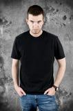 Ilsken man i svart t-skjorta på grungebakgrund Royaltyfria Bilder