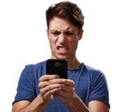Ilsken man med smartphonen arkivfoto