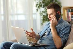 Ilsken man som hemma talar på telefonen royaltyfri bild