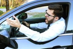 Ilsken man som kör en bil arkivfoton