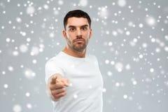 Ilsken man som pekar fingret till dig över snö Arkivfoto
