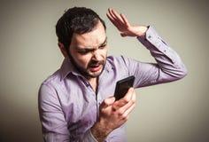 Ilsken man som ropar på telefonen Fotografering för Bildbyråer