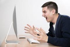 Ilsken man som skriker på datorskärmen Royaltyfria Bilder