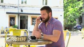 Ilsken man som talar vid smartphonen under frukosten i kafé arkivfilmer