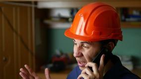 Ilsken manbyggnadsarbetare i en hardhat som ropar som talar på telefonsmartphonen Royaltyfria Foton