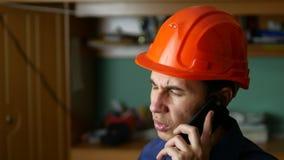 Ilsken manbyggnadsarbetare i en hardhat som ropar som talar på telefonsmartphonen Arkivbilder