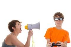 Ilsken moder av tonåriga spela dataspelar Royaltyfria Foton