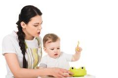 ilsken moder i förklädet som försöker att mata den lilla sonen som sitter i highchair fotografering för bildbyråer