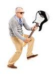 Ilsken mogen man som bryter en elektrisk gitarr royaltyfri bild
