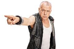 Ilsken mogen punkrock som pekar med hans hand Arkivbild