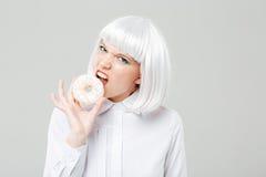Ilsken nätt ung kvinna med blont hår som äter den nya munken Royaltyfria Foton