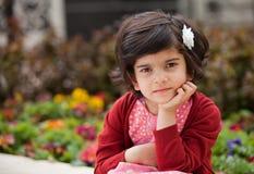 Ilsken och fundersam liten flicka i trädgården royaltyfri bild