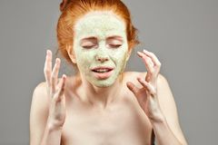 Ilsken olycklig ledsen ung kvinna med en grön leramaskering på hennes framsida royaltyfria foton