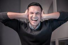 Ilsken olycklig man som har ett mycket stressigt jobb fotografering för bildbyråer