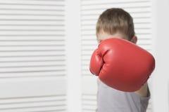 Ilsken pojke i röd boxninghandske hit arkivfoto