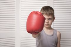 Ilsken pojke i röd boxninghandske hit royaltyfri foto