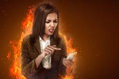 Ilsken seende mobiltelefon för affärskvinna Royaltyfri Foto