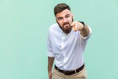 Ilsken skäggig affärsman med den vita skjortan som ser kameran och pekar fingret till dig royaltyfria bilder