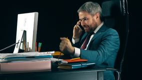 Ilsken skäggig affärsman som har emotionell stressig konversation på hans mobiltelefon Svart bakgrund video 4K stock video