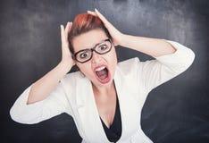 Ilsken skrikig lärare på svart tavlabakgrund arkivfoto