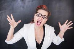 Ilsken skrikig lärare på svart tavlabakgrund arkivbild