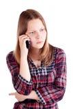 Ilsken tonårig flicka som talar på mobiltelefonen Arkivfoton