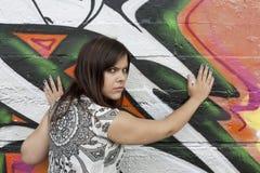 Ilsken ung kvinna mot grafittiväggen arkivfoto