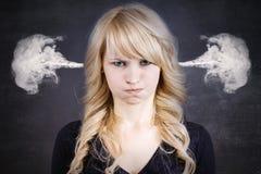 Ilsken ung kvinna som blåser ånga som kommer ut ur öron Fotografering för Bildbyråer
