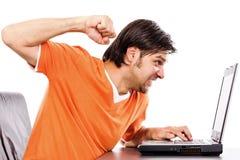 Ilsken ung man på bärbara datorn Royaltyfri Foto
