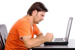 Ilsken ung man på hans bärbar dator Royaltyfri Bild