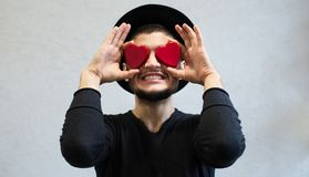 Ilsken ung man som rymmer röda hjärtor på hans ögon Hjärta för två rosa färg royaltyfri foto