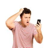 Ilsken ung man som talar på mobiltelefonen och som är hållande på till huvudet emotionell grabb på vit bakgrund arkivbilder