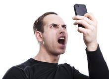 Ilsken ung man som talar på smartphonen arkivfoton