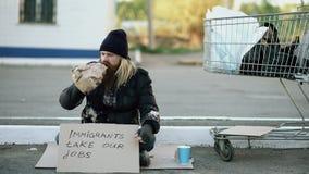 Ilsken uppriven ung hemlös man med papp som sitter nära shoppingvagnen och drinkalkohol på den kalla dagen på grund av stock video